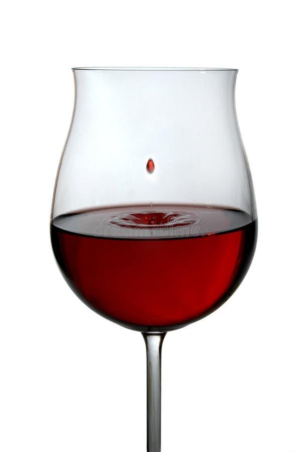 Vin rouge étant plu à torrents dans une glace de vin images libres de droits