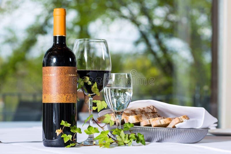 vin rouge avec la bouteille et le verre sur une table photo stock image du rouge dur e 33489198. Black Bedroom Furniture Sets. Home Design Ideas
