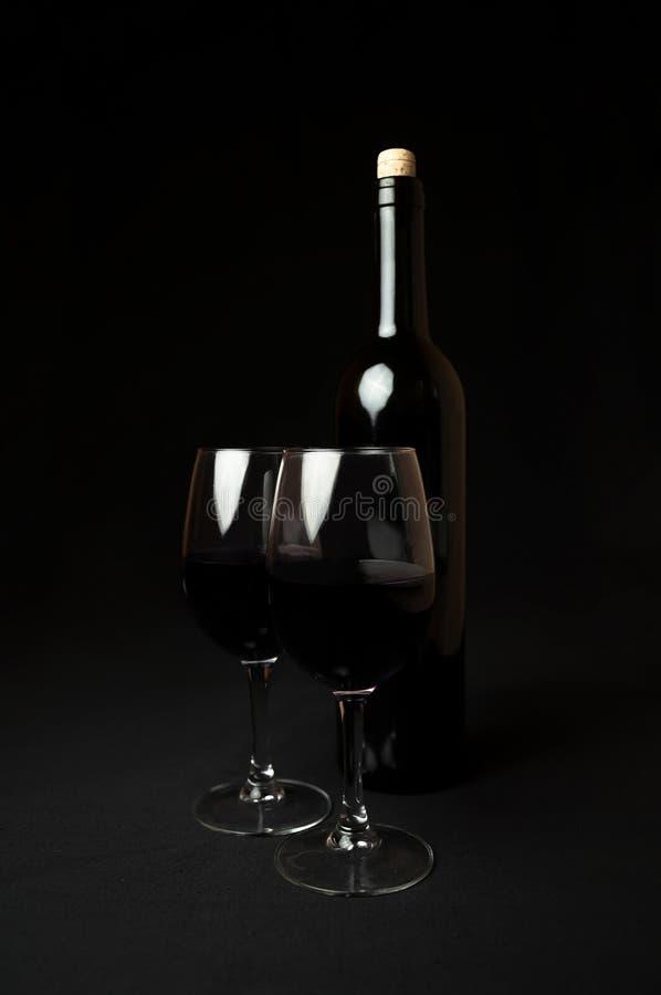 Vin rouge Bouteille et deux verres de vin rouge sur le fond noir photo stock