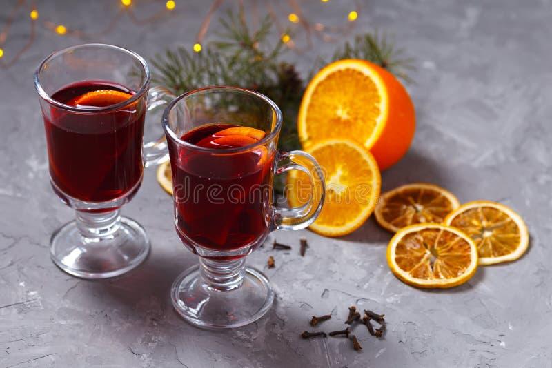 Vin rouge chauffé avec les épices et l'orange sur le fond foncé Boisson de chauffage photographie stock libre de droits