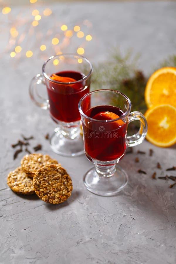 Vin rouge chauffé avec les épices et l'orange sur le fond foncé Boisson de chauffage image stock