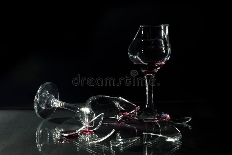 Vin rouge dans des tasses en verre cassées renversées sur le Tableau en verre d'isolement sur le noir images stock