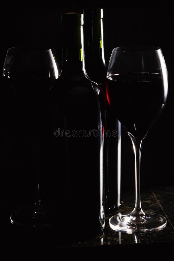 Vin rouge dans les glaces et des bouteilles photo stock