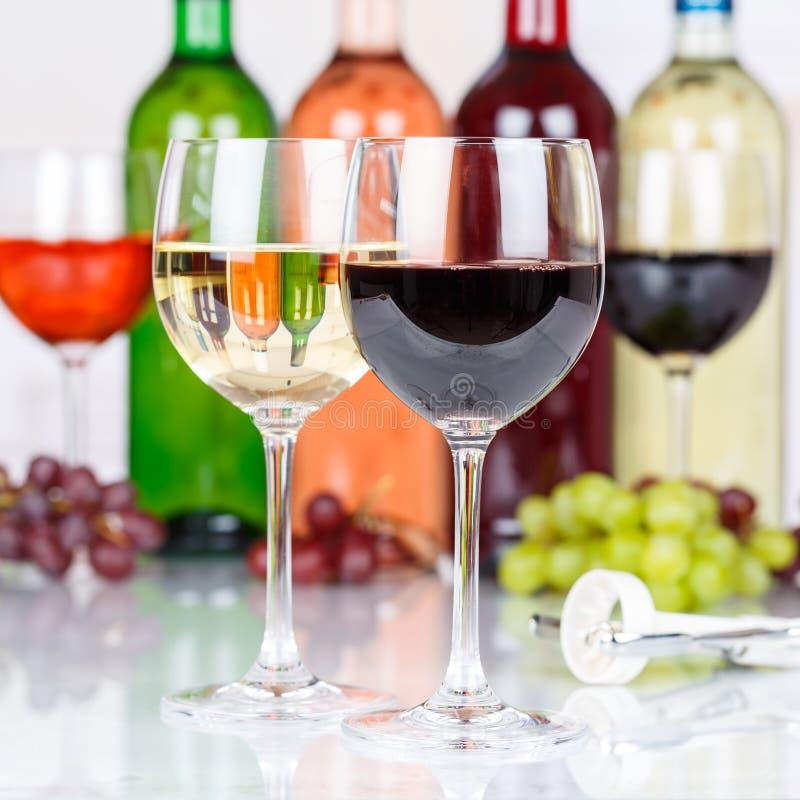 Vin rouge dans une place en verre de raisins images stock