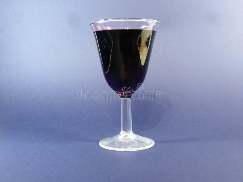 Vin rouge dans une tasse sur un blackground bleu photos libres de droits