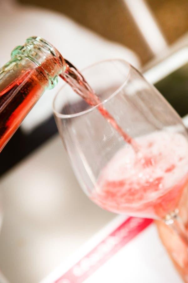 Vin rouge de versement d'une bouteille dans un échantillon de vin de verre à vin images stock