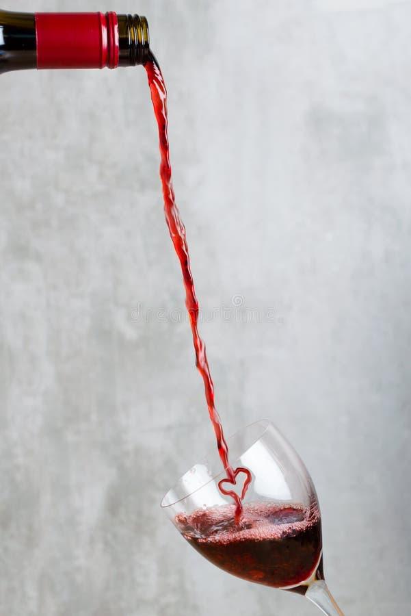 Vin rouge de versement formé comme coeur d'une bouteille dans un verre photos stock