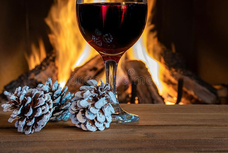 Vin rouge en verre avec cônes de pins de vacances photo libre de droits