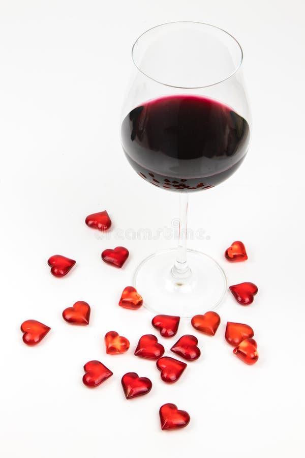Vin rouge en verre et coeurs rouges d'isolement sur le fond blanc - séduction romantique - jour de valentines photos libres de droits