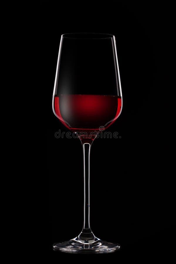 Vin rouge en verre sur le noir photo stock
