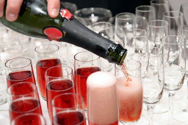 Vin rouge pleuvant à torrents dans la cuvette photographie stock