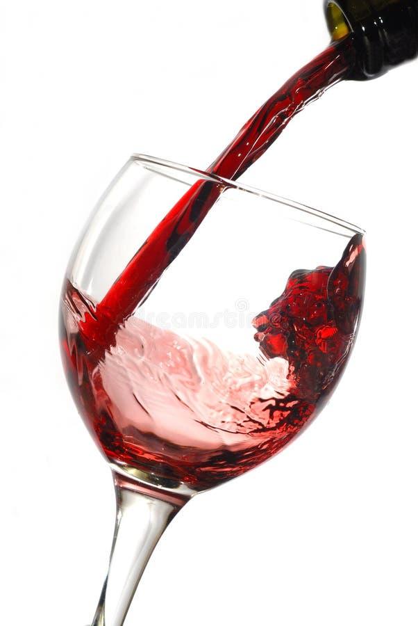 Vin rouge pleuvant à torrents vers le bas d'une bouteille photos libres de droits