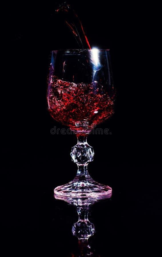 Vin rouge pleuvant ? torrents dans la glace de vin image stock