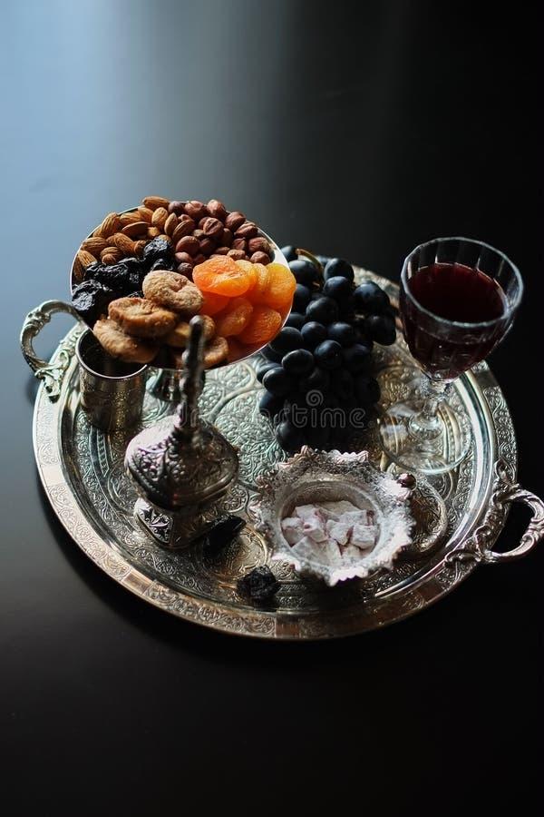 Vin rouge, verre à vin avec des noix, raisins et figues sur le fond en bois foncé images stock