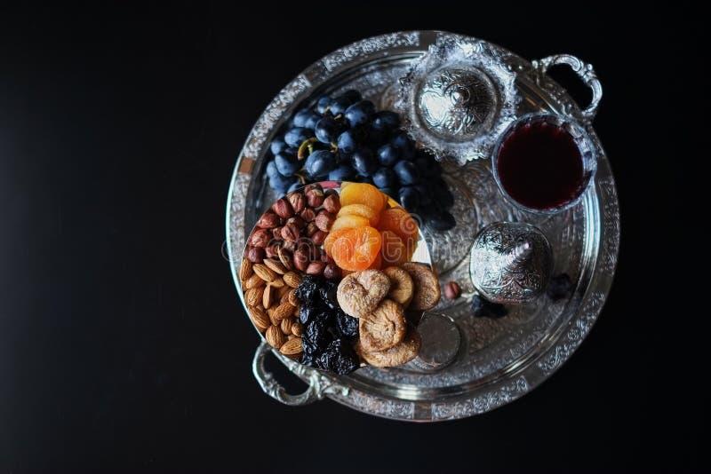 Vin rouge, verre à vin avec des noix, raisins et figues sur le fond en bois foncé photographie stock