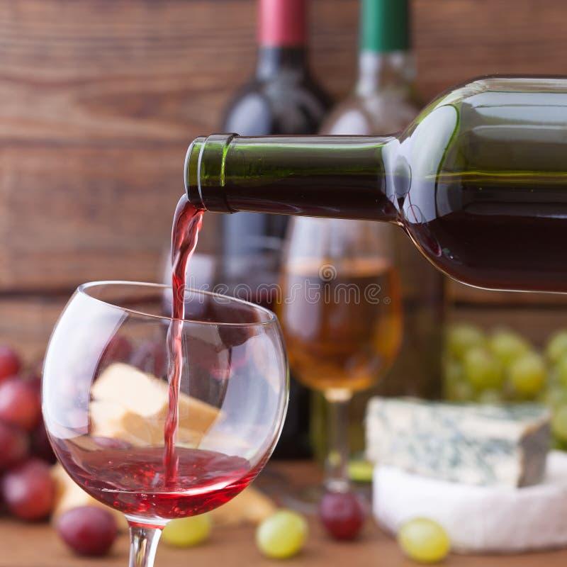 Vin rouge versant dans le verre, plan rapproché images stock