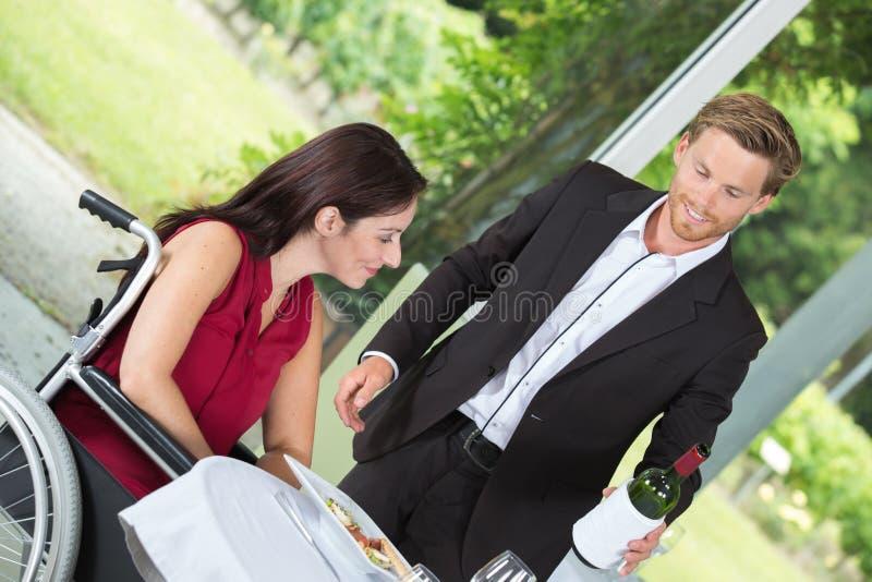 Vin servant de jeune serveur à la femme handicapée au restaurant image libre de droits