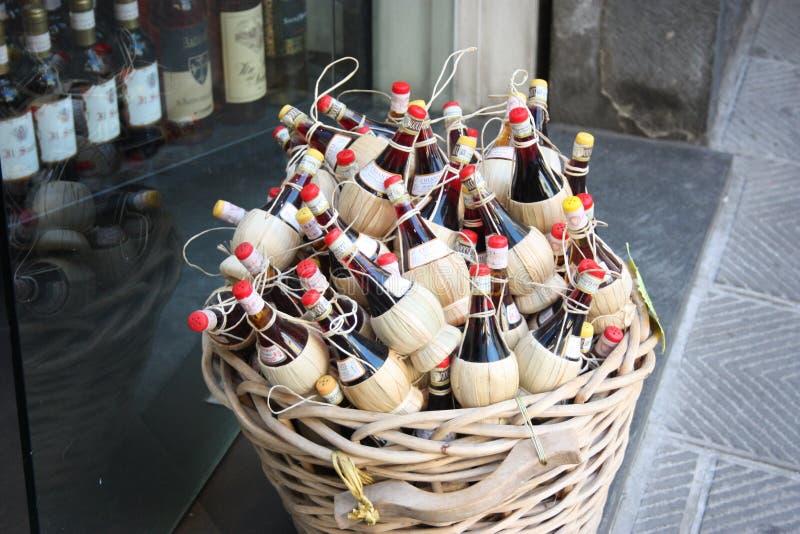 Vin toscan panier en osier montré sur la rue devant un magasin de bouteille de cru petits flacons de vin rouge local pour des sou images stock