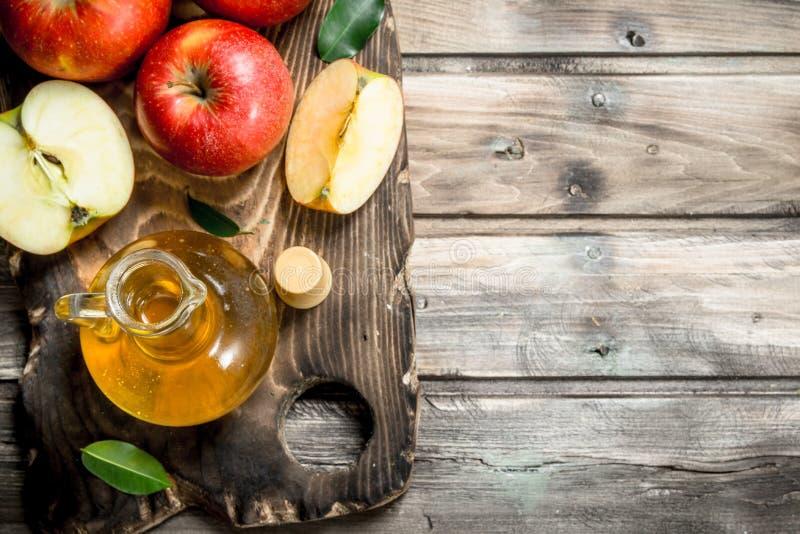 Vinagre de sidra de Apple con las manzanas rojas frescas en una tabla de cortar fotografía de archivo