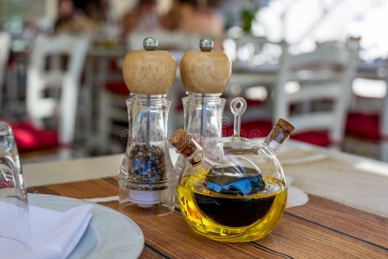 Vinagrera con el foco selectivo del aceite de oliva y del vinagre balsámico imagen de archivo