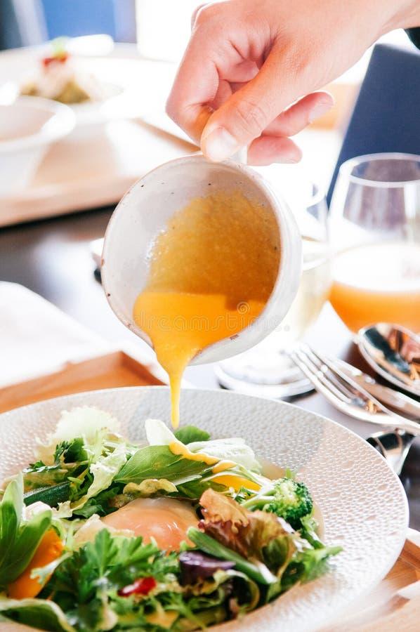 Vinagreta poner crema de colada que se viste en plato de la ensalada de la mezcla fotografía de archivo