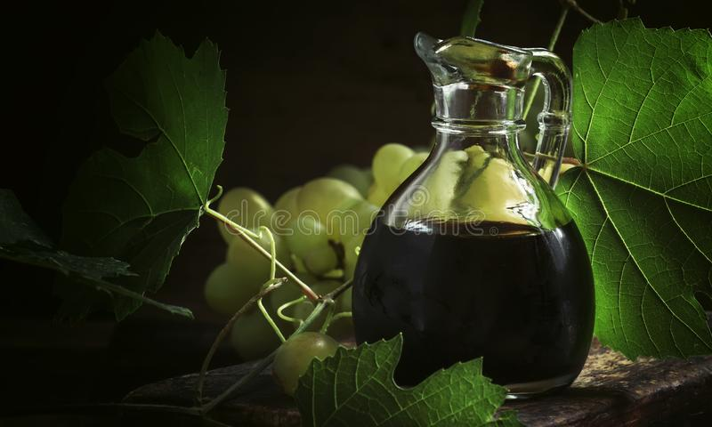 Vinaigre balsamique, fond rustique de table de cuisine de cru, toujours la vie, foyer sélectif photographie stock libre de droits