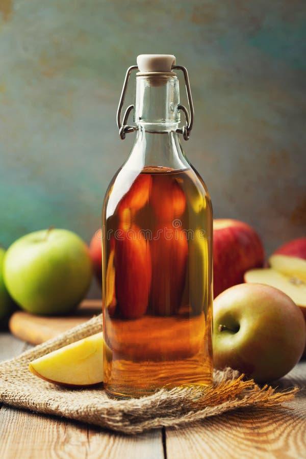 Vinaigre d'Apple Bouteille de vinaigre ou de cidre organique de pomme sur le fond en bois Aliment biologique sain images libres de droits