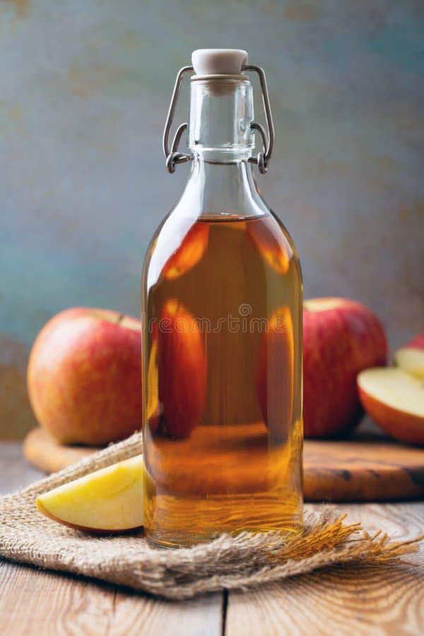 Vinaigre d'Apple Bouteille de vinaigre ou de cidre organique de pomme sur le fond en bois Aliment biologique sain photos stock