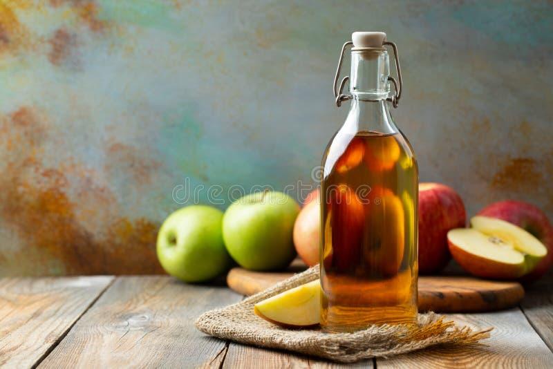 Vinaigre d'Apple Bouteille de vinaigre ou de cidre organique de pomme sur le fond en bois Aliment biologique sain Avec l'espace d photographie stock libre de droits