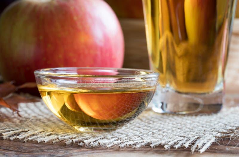 Vinaigre de cidre d'Apple dans un bol en verre, avec une pomme dans le backgr image stock