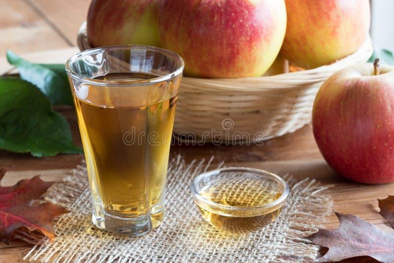 Vinaigre de cidre d'Apple dans un verre, avec des pommes à l'arrière-plan photos stock