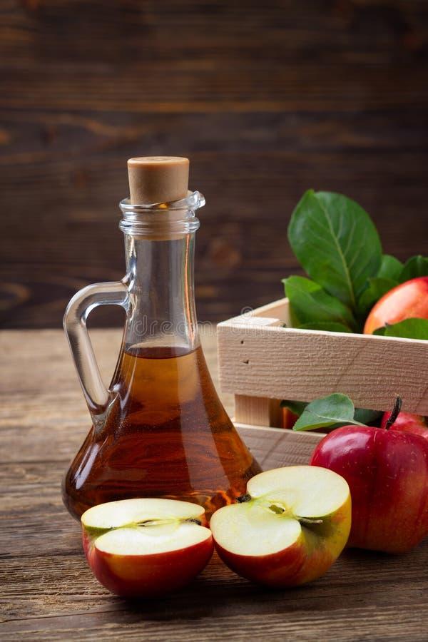 Vinaigre de cidre d'Apple et pomme rouge fraîche sur un fond en bois photos stock