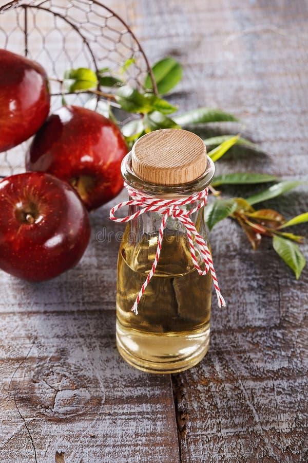 Vinaigre et pommes de cidre d'Apple au-dessus du fond en bois blanc image libre de droits