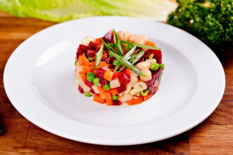 vinaigrette Cocina rusa tradicional Ensalada con la raíz hervida de la remolacha y verduras en la placa blanca imagen de archivo