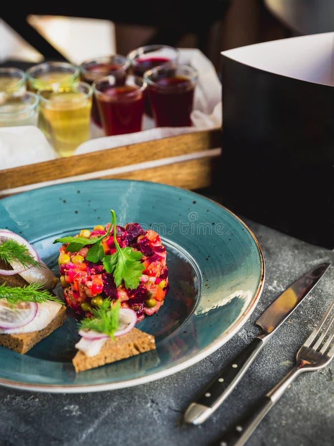 Vinaigrette de salade de betteraves, sandwichs avec des poissons, boissons alcoolisées et carte de papier noire de menu images libres de droits