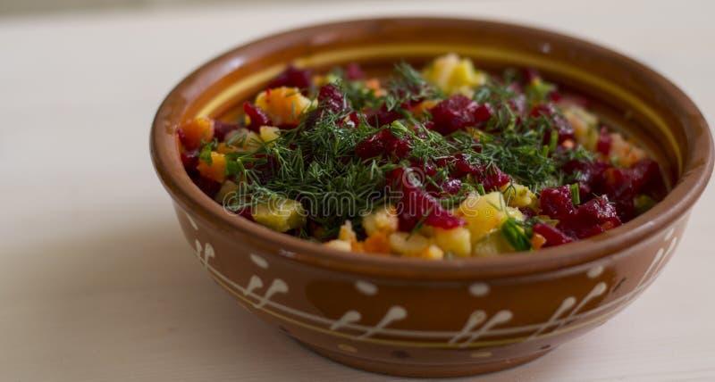 Vinaigrette dell'insalata sul piatto sulla tavola fotografia stock
