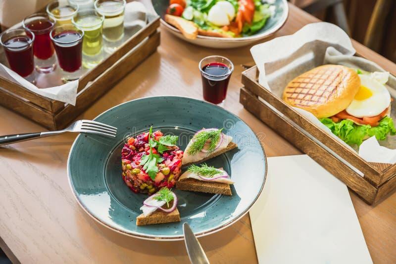 Vinaigrettesalade, Amerikaanse hamburger met ei, Caesar-salade en dranken op lijst in koffie stock afbeeldingen