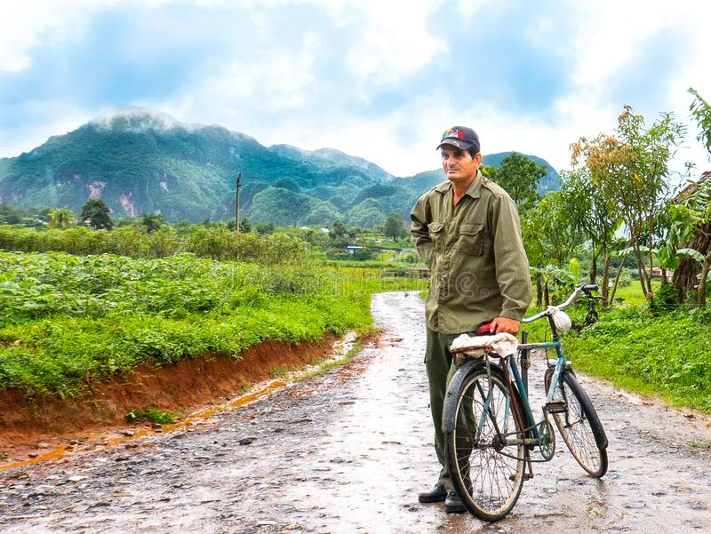 Vinales, Cuba. June 2016: Cuban man with bicycle, coming back from tobacco plantations, surrounded by green fields. stock images