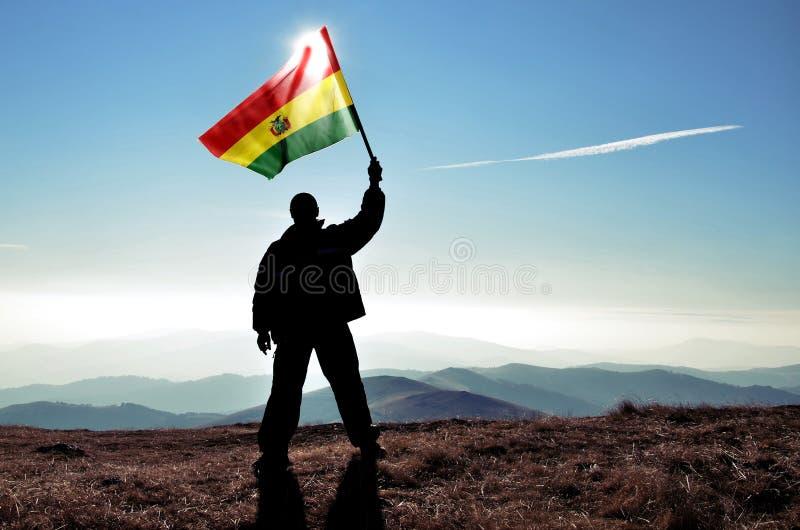 Vincitore dell'uomo che ondeggia la bandiera della Bolivia sopra il picco di montagna immagine stock libera da diritti