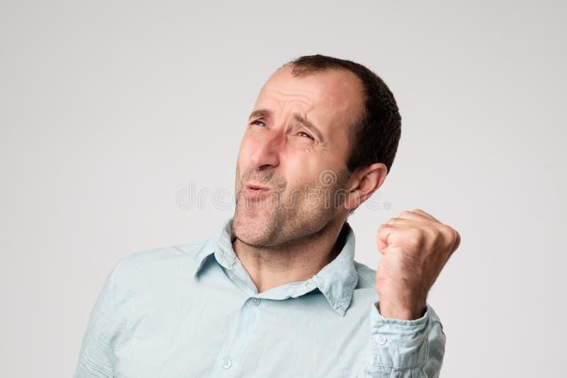 Vincitore maschio ispanico maturo fortunato felice che esclama, rallegrandosi al suo successo sul lavoro, ad esempio sì, pugno di immagine stock