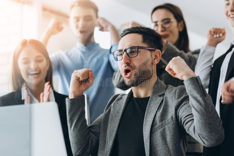 Vincitori di ogni giorno Gruppo di gente di affari felice nell'abbigliamento casual astuto che esamina il computer portatile e ge fotografie stock