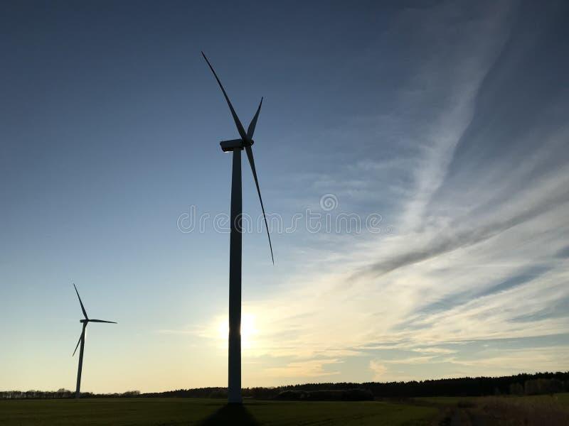 Vind- eller vindturbin med inställd sol bakom och copyspace royaltyfri fotografi
