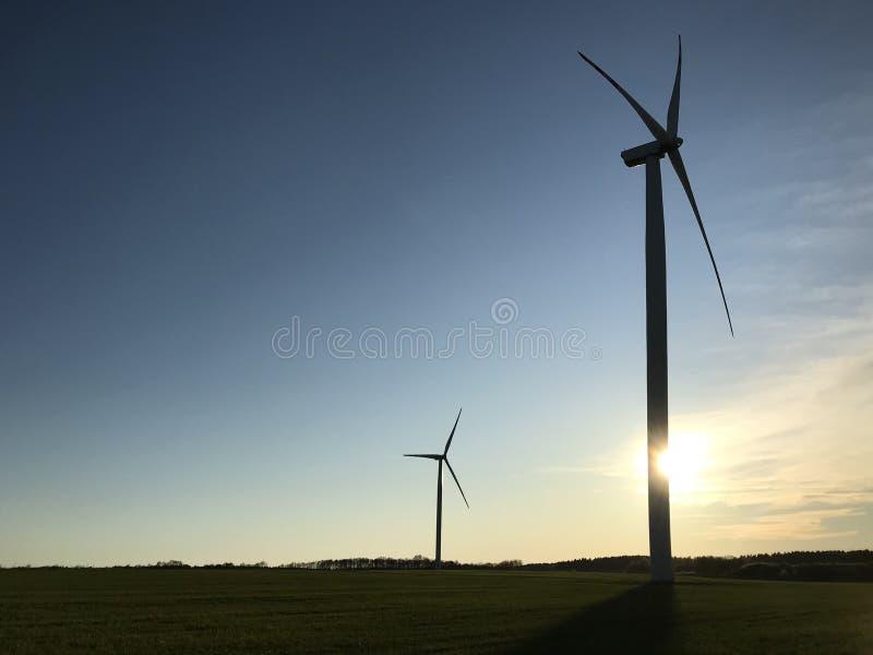 Vind- eller vindturbin med inställd sol bakom och copyspace royaltyfri bild