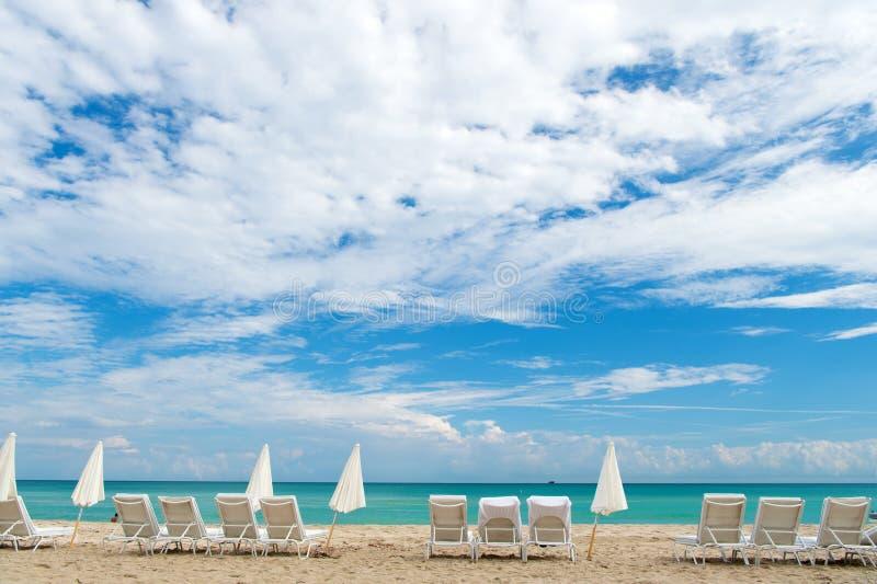 Vind grote waarden in glitzy Zuidenstrand Het zuidenstrand van Miami Sunbeds en paraplu's op zandig strand De Reis van Florida wa stock afbeelding