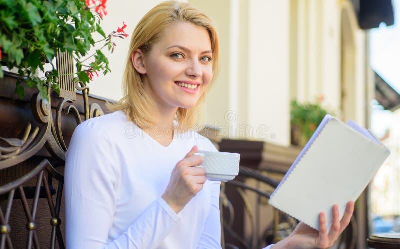 Vind kans om meer te lezen Het meisje drinkt koffie terwijl gelezen best-sellerboek door populaire auteur Mokkoffie en royalty-vrije stock afbeeldingen