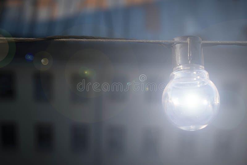 Vind-stil den elektriska lampan glöder med ett ljust blått ljus mot bakgrunden av huset Tänder vägen royaltyfri bild
