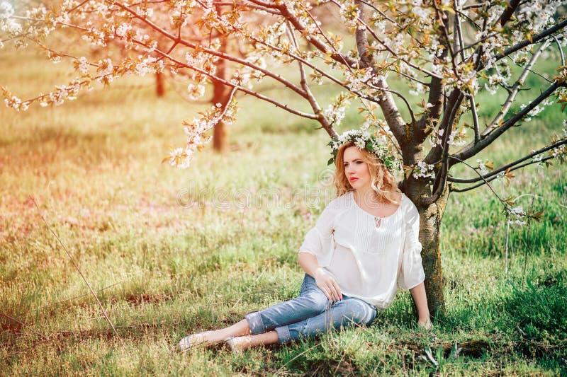 Vinda da mola! Mulher gravida alegre nova bonita em flores da grinalda na barriga tocante principal ao sentar-se perto da árvore  foto de stock