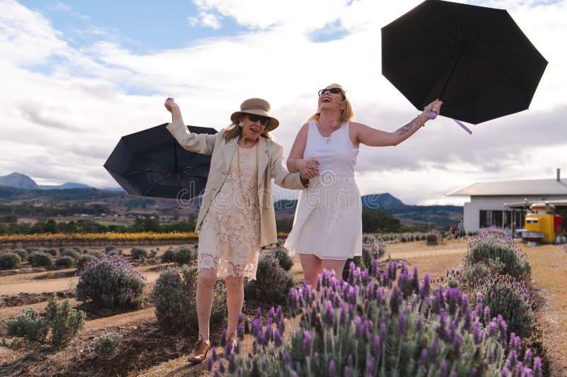 Vindblåsande paraplyer Moder till Bride och dotters vineribröllop royaltyfri fotografi