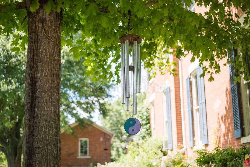 Vindchime på ett träd i en trädgård fotografering för bildbyråer