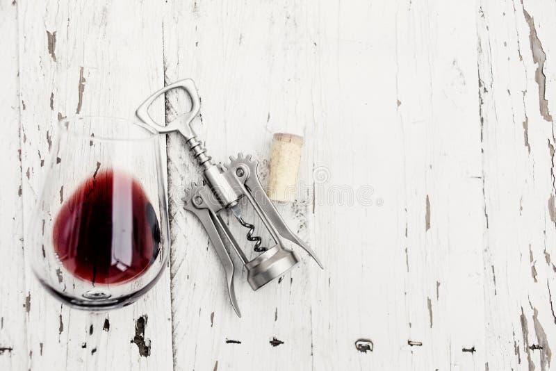 Vindegustationbegrepp - rött vinexponeringsglas, vinkorkar och Co arkivbild